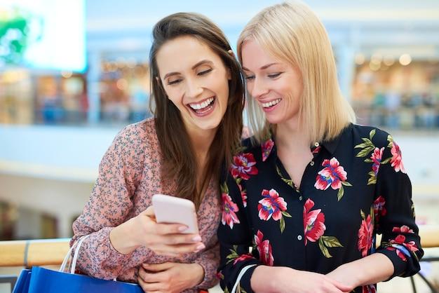 Glückliche freunde, die beim einkaufen im einkaufszentrum handy benutzen