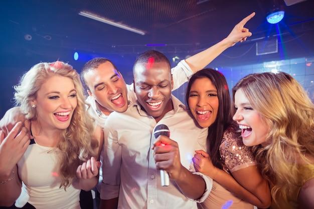 Glückliche freunde, die beim karaoke singen