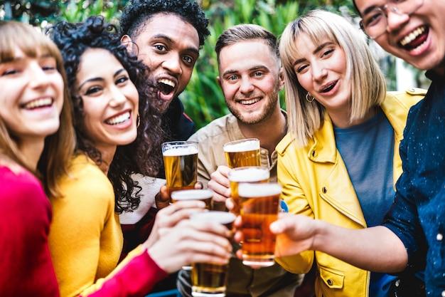 Glückliche freunde, die bier an der brauerei-bar dehor rösten - freundschaftslebensstilkonzept mit jungen tausendjährigen leuten, die zeit zusammen im freiluft-pub genießen