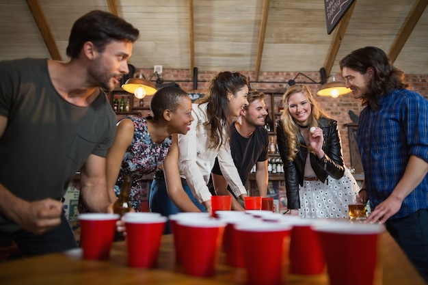 Glückliche freunde, die bier-pong-spiel in der bar spielen