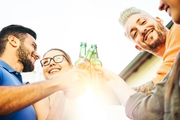 Glückliche freunde, die biere bei dem sonnenuntergang im freien rösten