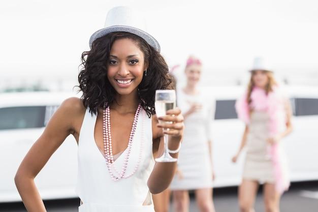 Glückliche freunde, die champagner vor einer limousine trinken