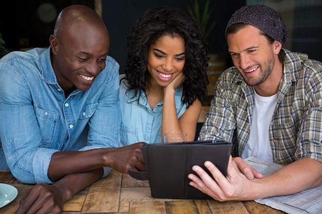 Glückliche freunde, die digitales tablett am tisch im kaffeehaus verwenden