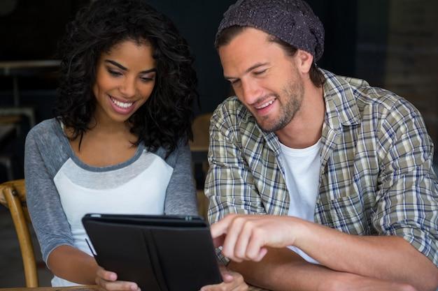 Glückliche freunde, die digitales tablett im kaffeehaus verwenden