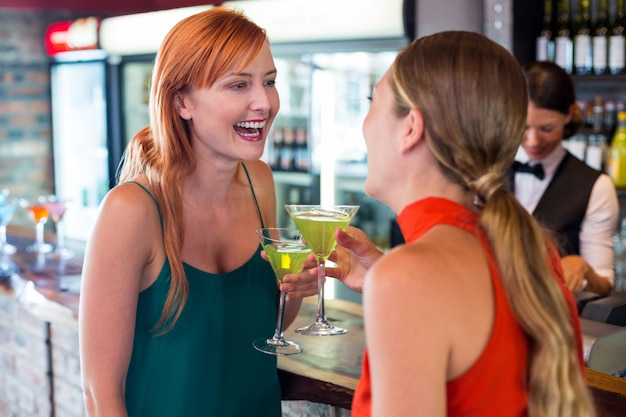 Glückliche freunde, die ein cocktail vor barzähler halten