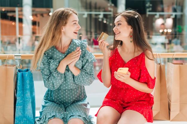 Glückliche freunde, die einander sitzen und betrachten