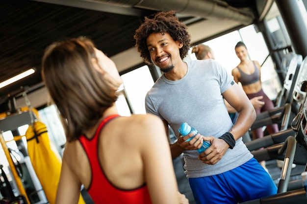 Glückliche freunde, die eine pause beim chatten im fitnessstudio genießen