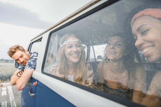 Glückliche freunde, die einen vintagen minivan fahren