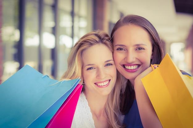 Glückliche freunde, die einkaufstaschen halten