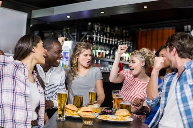 Glückliche freunde, die etwas trinken und sport aufpassen