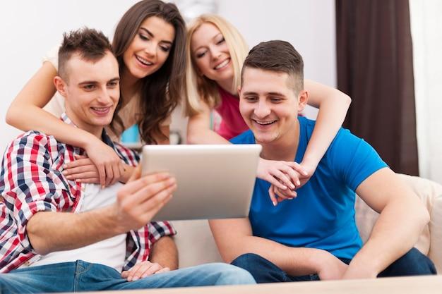 Glückliche freunde, die freizeit verbringen und digitales tablet zu hause verwenden