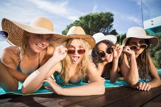 Glückliche freunde, die im swimmingpool genießen
