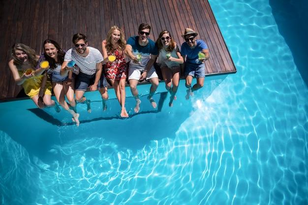 Glückliche freunde, die im swimmingpool sitzen