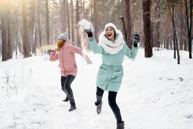 Glückliche freunde, die im winter draußen mit schnee spielen