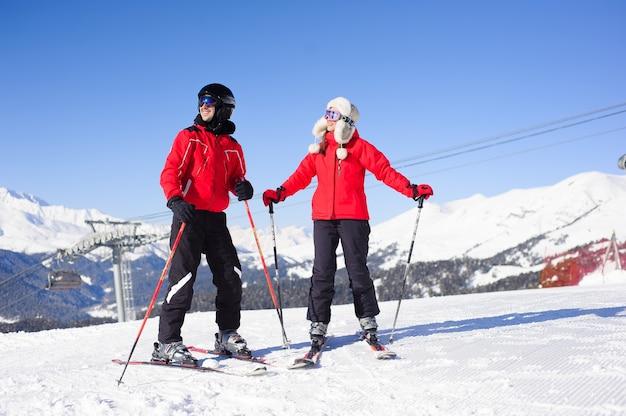 Glückliche freunde, die in den winterferien ski fahren - junge coulpe, die spaß am extremsport haben - freundschafts- und ferienkonzept
