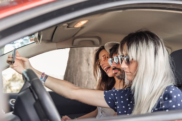 Glückliche freunde, die innerhalb des autos selfie durch handy nehmend sitzen