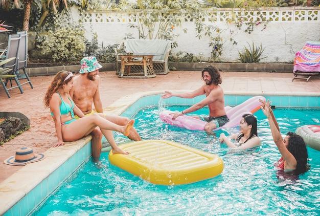 Glückliche freunde, die mit luft lilo ball an der schwimmbadparty schwimmen - junge leute, die spaß in den sommerferienferien haben