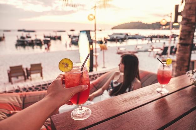 Glückliche freunde, die mit tropischen cocktails auf der strandparty zujubeln