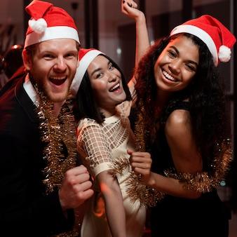 Glückliche freunde, die mit weihnachtsmützen feiern
