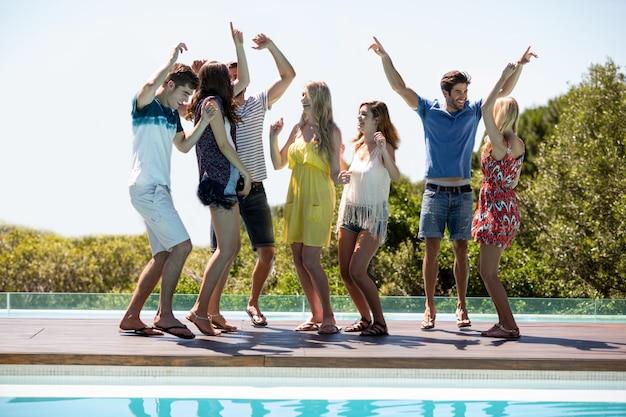 Glückliche freunde, die nahe dem swimmingpool tanzen