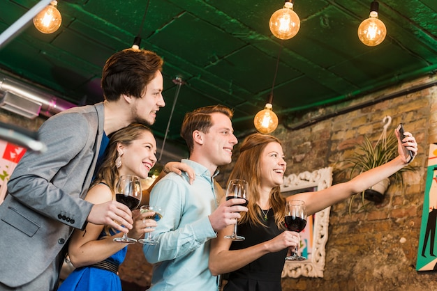 Glückliche freunde, die selfie auf mobiltelefon am cocktailbarrestaurant nehmen