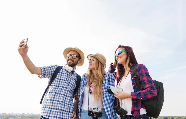 Glückliche freunde, die selfie auf smartphone an draußen nehmen