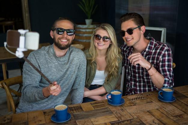 Glückliche freunde, die selfie mit einbeinstativ am tisch im coffeeshop nehmen