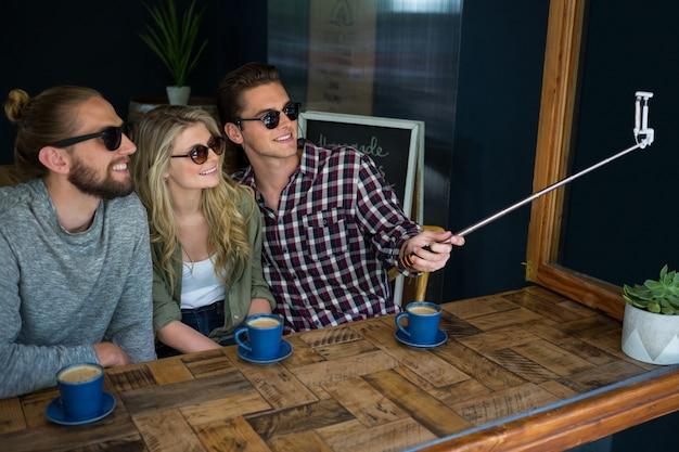 Glückliche freunde, die selfie mit einbeinstativ am tisch in der cafeteria nehmen