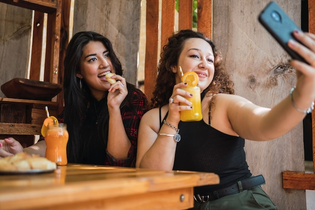 Glückliche freunde, die selfie mit ihren handys herausnehmen, während sie fruchtsäfte an der bar trinken.
