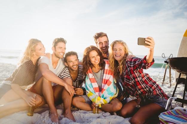 Glückliche freunde, die selfie mit smartphone nehmen