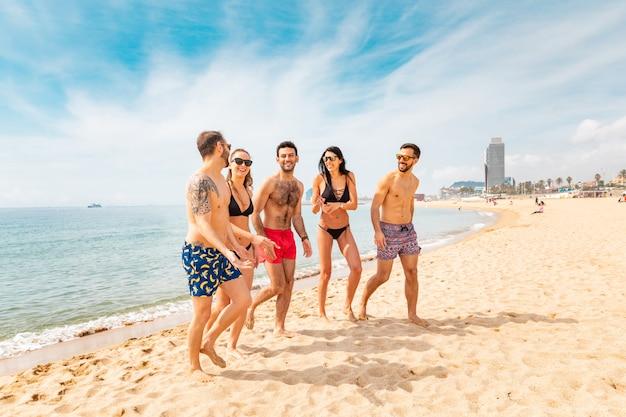 Glückliche freunde, die spaß am strand in barcelona haben