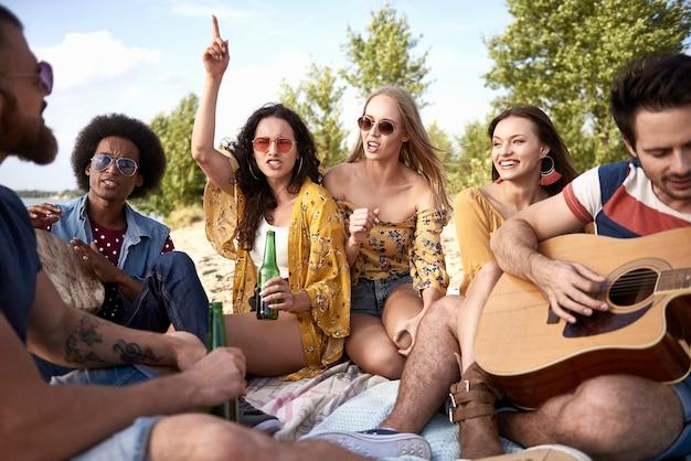 Glückliche freunde, die spaß am strand mit musikinstrumenten haben