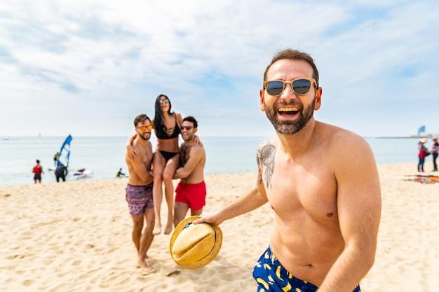 Glückliche freunde, die spaß am strand von barcelona haben