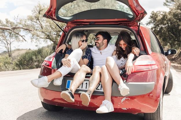 Glückliche freunde, die spaß im autokofferraum auf straße machen