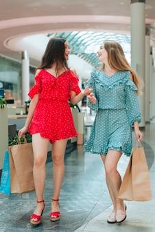 Glückliche freunde, die spaß im einkaufszentrum haben