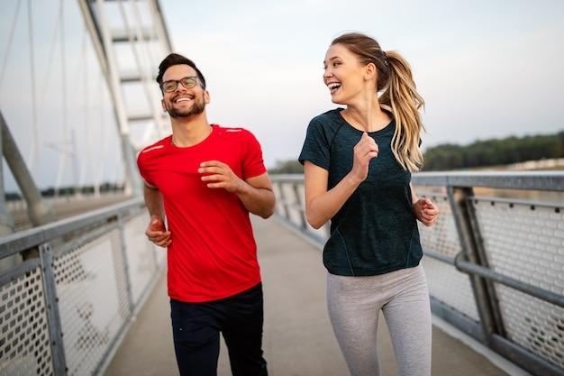 Glückliche freunde, die über die brücke laufen. gesunder lebensstil leben.