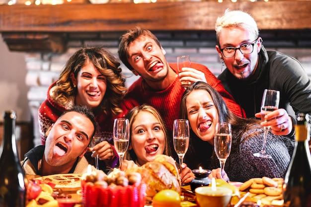 Glückliche freunde, die verrücktes betrunkenes selfie nehmen, das weihnachtszeit mit champagner feiert