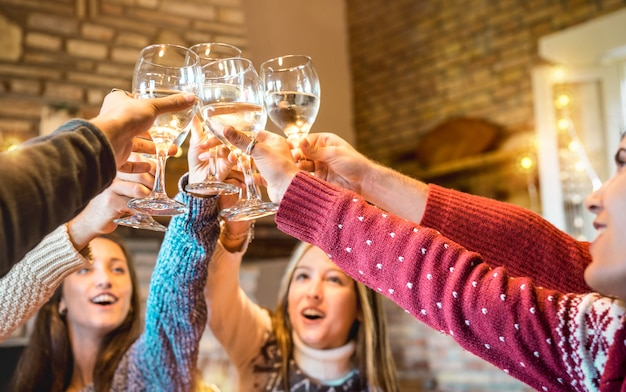 Glückliche freunde, die weihnachten feiern, champagnerwein zu hause röstend abendessen