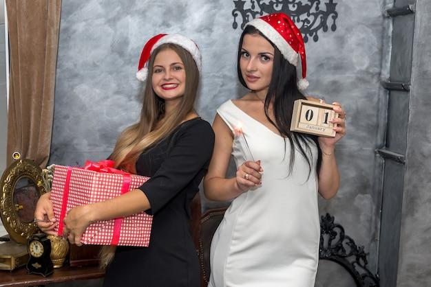 Glückliche freunde, die weihnachten mit geschenkbox feiern