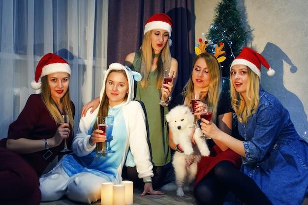 Glückliche freunde, die weihnachten oder neujahr mit einem glas champagner und toasten feiern. fünf schöne mädchen, die zu hause weihnachten feiern