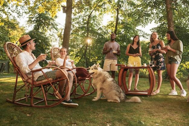 Glückliche freunde essen und trinken bier beim grillabendessen bei sonnenuntergang
