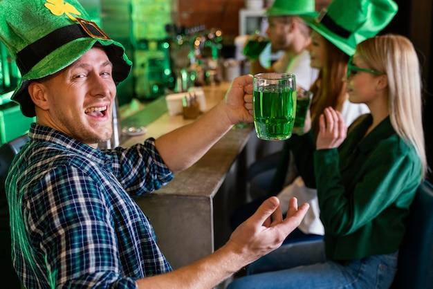 Glückliche freunde feiern st. patricks gemeinsamer tag an der bar
