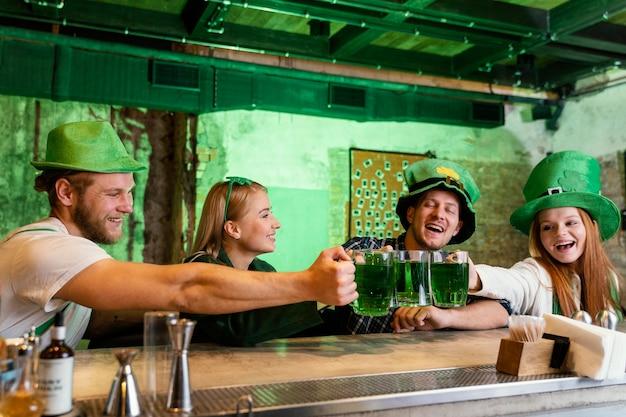 Glückliche freunde feiern st. patricks tag zusammen mit einem drink an der bar