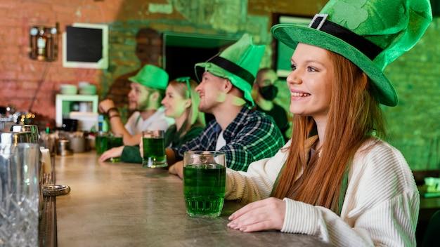 Glückliche freunde feiern st. patricks tag zusammen mit getränken