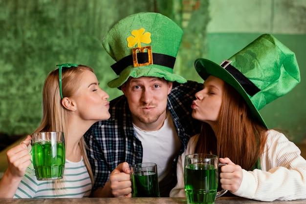 Glückliche freunde feiern zusammen st. patricks tag an der bar mit getränken