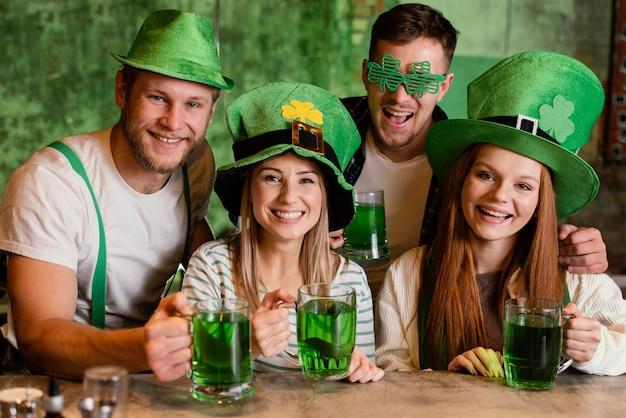 Glückliche freunde feiern zusammen st. patricks tag an der bar