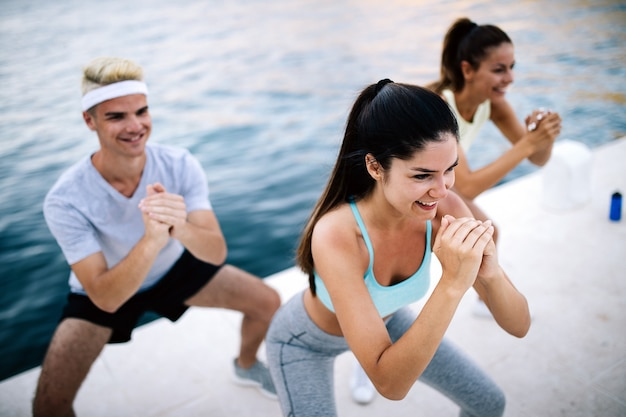Glückliche freunde fitnesstraining zusammen im freien aktiv gesund leben