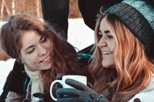 Glückliche freunde im winterwald im auto. zwei glückliche mädchen sitzen im kofferraum eines autos, trinken kaffee aus einer thermoskanne, reden und lachen.