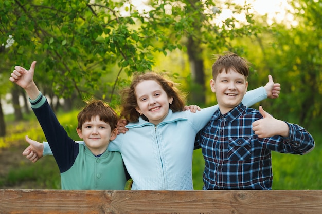 Glückliche freunde kinder hände hoch und zeigen positive emotionen.