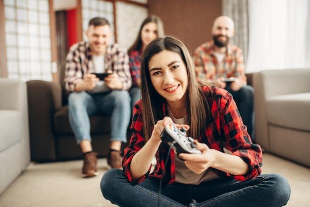 Glückliche freunde mit joysticks spielen videokonsole zu hause. eine gruppe von spielern, die videospiele spielen, männliche und weibliche spieler haben einen wettbewerb